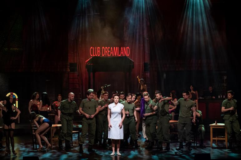 Fotografia przedstawia dynamiczną sytuację w nocnym klubie Dreamland w Sajgonie. Na tle roztańczonych, rozbawionych amerykańskich żołnierzy  z tancerkami klubu, w białej orientalnej sukience stoi  główna bohaterka Kim. Jest smutna i zagubiona. Na uboczu stoi zamyślony żołnierz, który bacznie ją obserwuje.