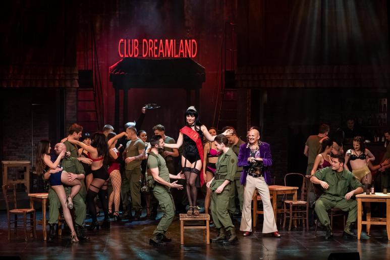 Fotografia przedstawia  bawiących się amerykańskich żołnierzy z prostytutkami nocnego klubu Dreamland w Sajgonie. Pośród roztańczonych par widzimy stojącą na drewnianym stołku prostytutkę Gigi, która zostaje tej nocy wybrana na Miss Saigonu.