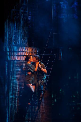 Fotografia przedstawia zakochaną parę, Kim i Chrisa, siedzących na schodach i czule całujących się.