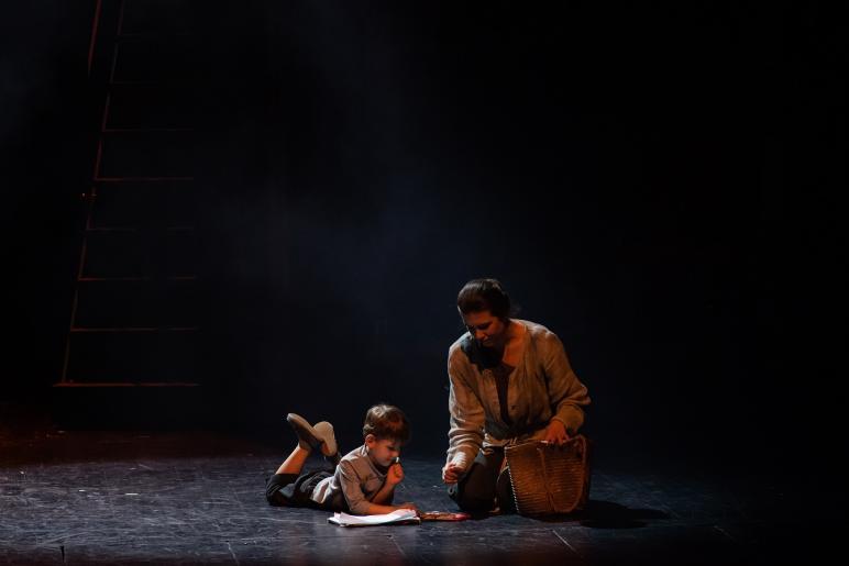 Fotografia przedstawia kobietę - Kim i bawiące się dziecko. Oboje siedzą na podłodze. Chłopiec około lat 3 rysuje obrazek kredkami.