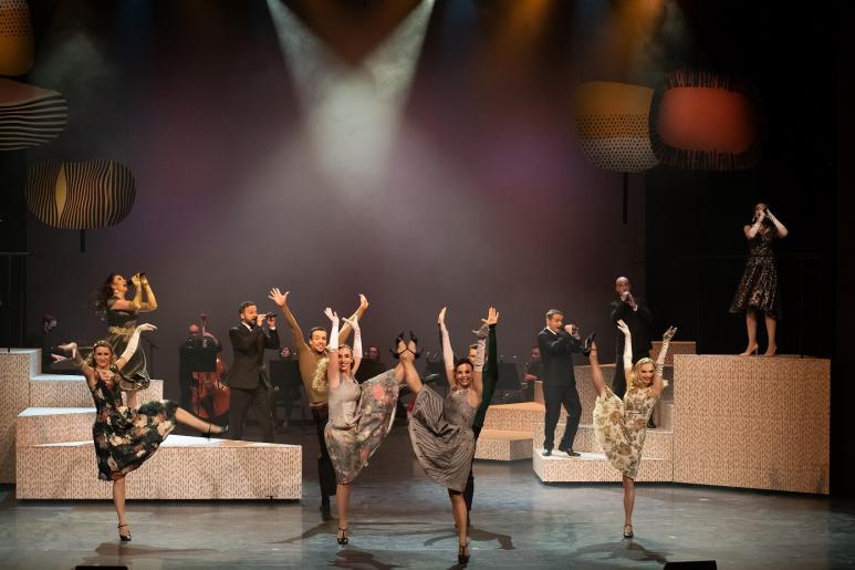 Fotografia przedstawia na pierwszym planie cztery tańczące kobiety, każda z nich ma wysoko podniesioną do góry nogę. Za ich plecami widzimy śpiewających trzech mężczyzn i śpiewające dwie kobiety oraz w tle zespół muzyczny grający na instrumentach.
