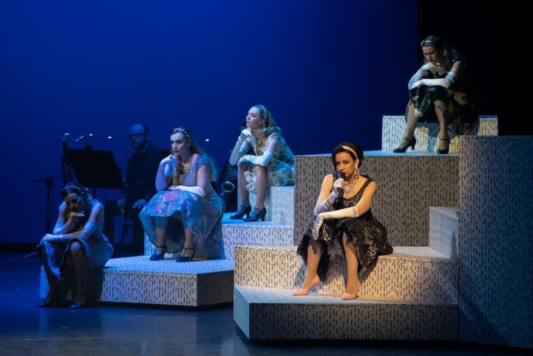 Fotografia przedstawia pięć kobiet siedzących na schodach, wszystkie mają znudzone miny. Jedna z nich trzyma mikrofon. W tle widoczny jest także mężczyzna siedzący przed pulpitem z nutami. W dłoniach trzyma klarnet.