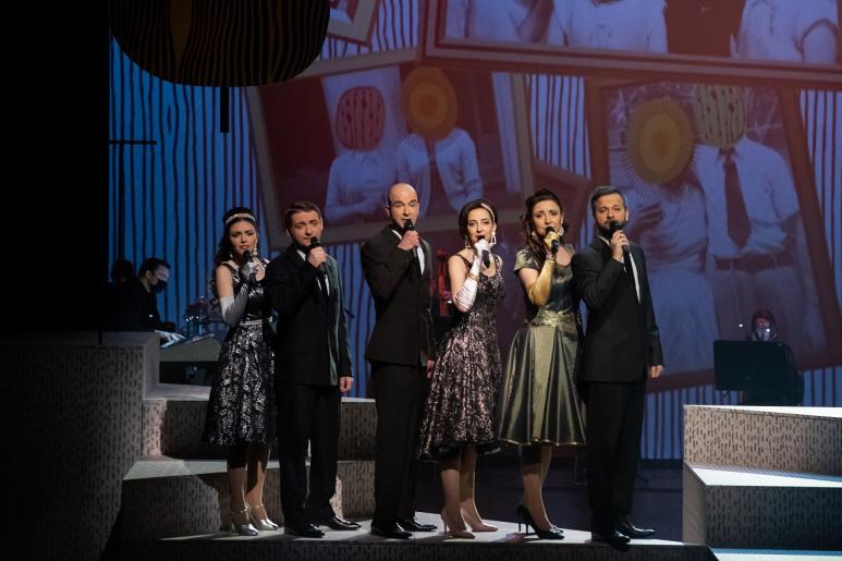 Fotografia przedstawia trzech mężczyzn i trzy kobiety, wszyscy mają mikrofony w dłoniach do których śpiewają. Kobiety ubrane są w wieczorowe sukienki, natomiast mężczyźni w czarne garnitury. W tle widać zespół muzyczny grający na instrumentach.