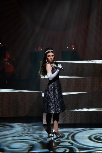 Zdjęcie przedstawia kobietę ubraną w wieczorową sukienkę, w ręku trzyma mikrofon, patrzy się odważenie w dal. W tle widać zespół muzyczny grający na instrumentach.