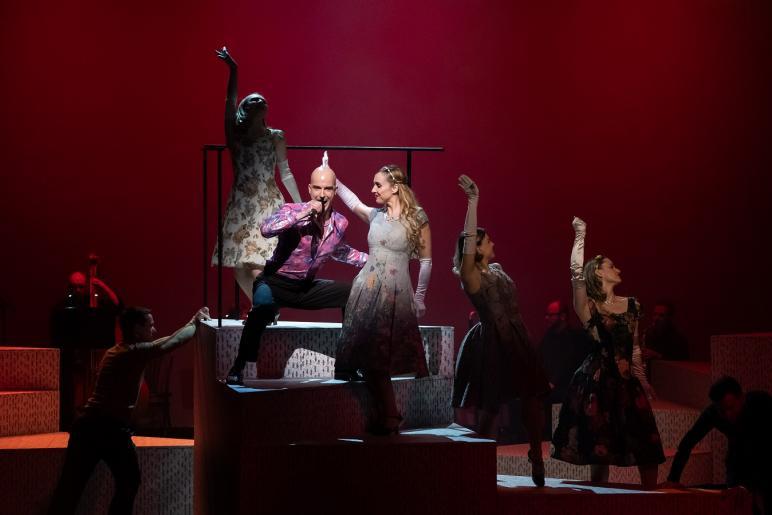 Fotografia przedstawia śpiewającego mężczyznę oraz cztery kobiety tańczące wokół niego. Wszyscy znajdują się na schodach, które przesuwane są przez dwóch mężczyzn. W tle widać zespól grający na instrumentach.