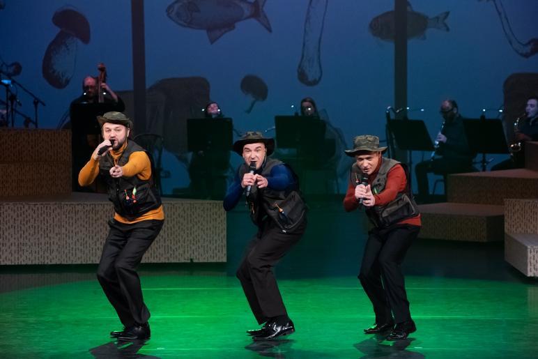 Fotografia przedstawia trzech mężczyzn śpiewających do mikrofonów, są oni pochyleni do połowy. Mężczyźni ubrani są czarne spodnie, oraz wędkarskie kamizelki i kapelusze. W tle widać grający zespół na instrumentach.