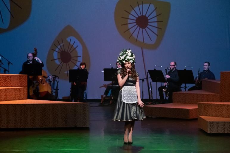Fotografia przedstawia kobietę śpiewającą do trzymanego mikrofonu. Kobieta jest ubrana w srebrzysta sukienkę i biały fartuszek, na głowie ma kapelusz/czepek z  kwiatów. W tle widać zespół muzyczny grający na instrumentach.