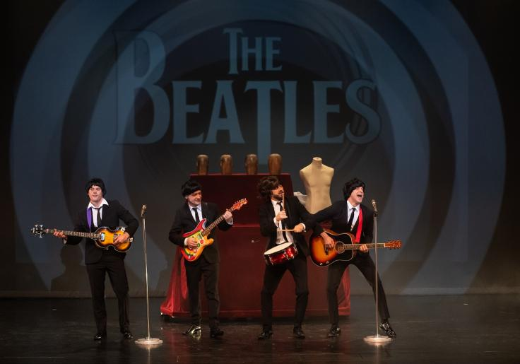 """Na kolorowym zdjęciu widzimy trzech mężczyzn grających na gitarach i jednego na bębenku. Stylizowani są na Beatlesów, ubrani w czarne garnitury. Mężczyźni występują na scenie śpiewając do mikrofonów. W tle za nimi wyświetla się napis \""""The Beatles\""""."""