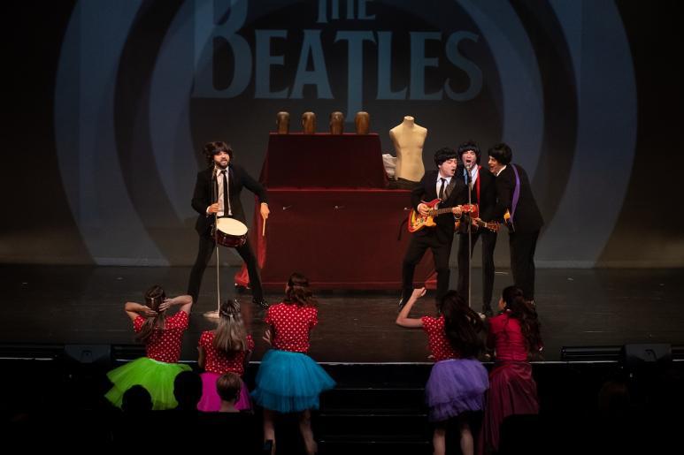 """Na kolorowym zdjęciu widzimy trzech mężczyzn grających na gitarach i śpiewających do jednego mikrofonu, czwarty mężczyzna ekspresyjnie gra na bębenku. Mężczyźni stylizowani są na Beatlesów, ubrani w czarne garnitury.  W tle za nimi wyświetla się napis \""""The Beatles\"""". Przed sceną widzimy pięć roztańczonych kobiet ubrane w kolorowe spódniczki i czerwone bluzki w białe groszki."""