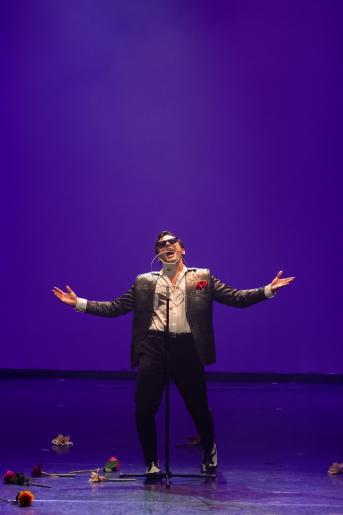 Na kolorowym zdjęciu widzimy mężczyznę w ciemnych okularach  stylizowanego na Marino Marini. Mężczyzna stoi samotnie na scenie, ma rozłożenie ręce, śpiewa ekspresyjnie do mikrofonu. Na scenie wokół jego stóp leżą kwiaty, rzucone przez jego fanki.
