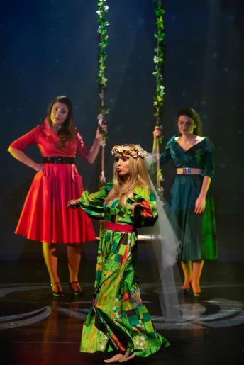 Na kolorowym zdjęciu widzimy trzy kobiety. Jedna z nich stylizowana jest na  Marylę Rodowicz. Kobieta ma długą kolorową sukienkę w dominującym zielonym kolorze, na włosach ma wianek z welonem. Pozostałe dwie kobiety ubrane są w jednobarwne rozkloszowane sukienki, trzymają huśtawkę, która jest za plecami pierwszej kobiety.