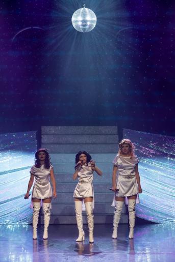 Na kolorowym zdjęciu widzimy trzy kobiety, które są stylizowane na wokalistki zespołu ABBA. Kobiety ubrane są w charakterystyczne krótkie białe sukienki i długie białe kozaki. Wszystkie trzy trzymają mikrofony, natomiast jedna z nich śpiewa. Za ich plecami stoją srebrzyste schody, nad nimi wisi dyskotekowa srebrna kula.