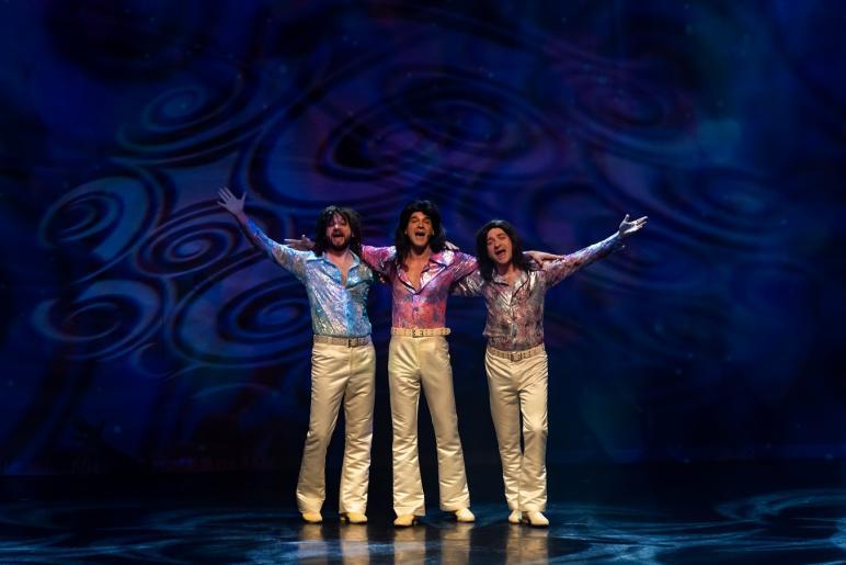 Na kolorowym zdjęciu widzimy trzech rozśpiewanych mężczyzn trzymających się za ramiona. Mężczyźni stylizowani są na członków zespołu Bee Gees. Ubrani są w długie, białe dzwony oraz kolorowe rozpięte do połowy koszule.
