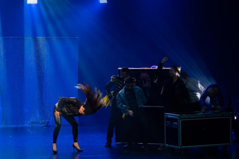 """Na kolorowym zdjęciu widzimy grupę 6 osób tańczących w rytm w muzyki do utworu \""""The final countdown story\"""" zespołu Europe. Jedna z kobiet na scenie ubrana jest w skórzane spodnie i kurtkę, wymachując długimi włosami śpiewa wspomnianą piosenkę."""