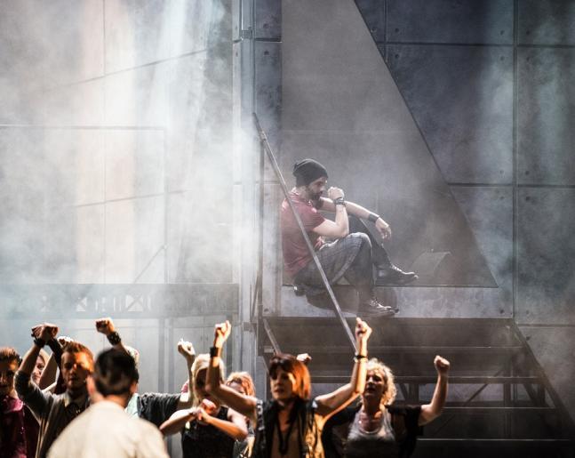 Zdjęcie przedstawia zadumanego mężczyznę siedzącego na schodach, jest to aktor odgrywający rolę Judasza. Widoczny jest także tłum ludzi wiwatujący na cześć aktora odgrywającego role Jezusa.