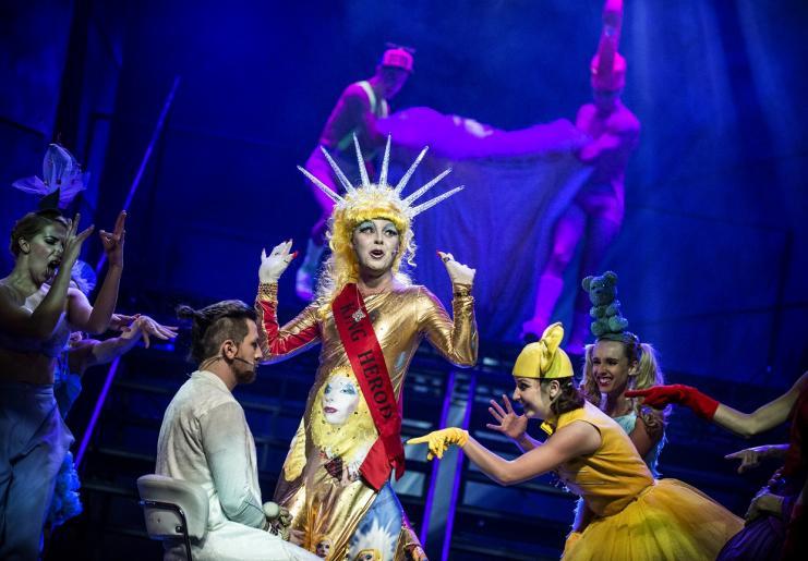 Zdjęcie przedstawia aktorów odgrywających rolę Jezusa i króla Heroda oraz jego poddanych. Herod ubrany jest w złotą suknię z wyraźnym makijażem na twarzy, natomiast aktor odgrywający Jezusa siedzi przed nim na obrotowym krześle.