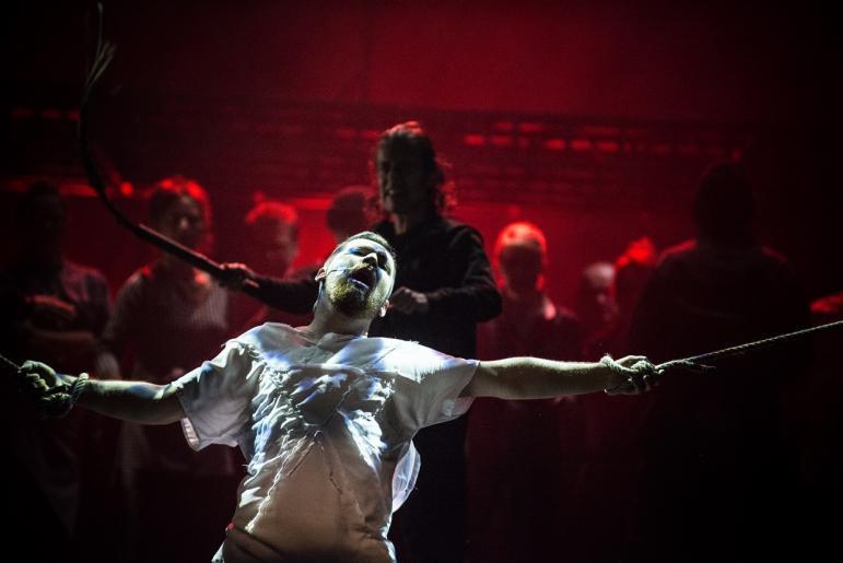 Na zdjęciu widzimy aktora odgrywającego rolę Jezusa, który jest biczowany przez mężczyznę widocznego w tle.