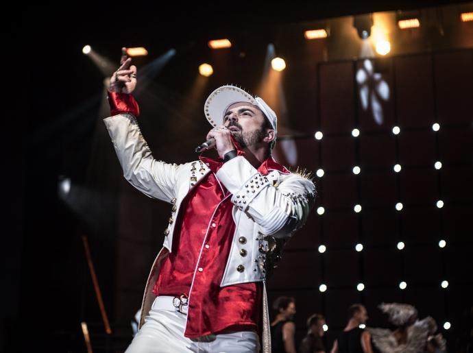 Zdjęcie przedstawia śpiewającego aktora odgrywającego rolę Judasza. Mężczyzna ubrany jest w czerwoną koszulę oraz biały garnitur w rockowym stylu. Ma również białą czapkę z daszkiem z widocznymi ćwiekami.
