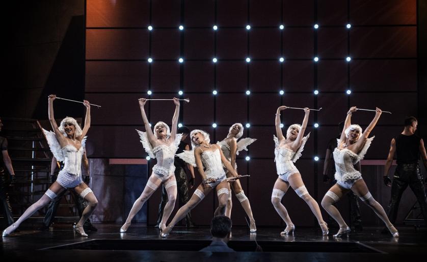 Fotografia przedstawia sześć tańczących aktorek odgrywających rolę aniołków. Kobiety ubrane są białe pończochy, białe body. Widoczne są u każdej z nich białe skrzydła i białe peruki na głowach.