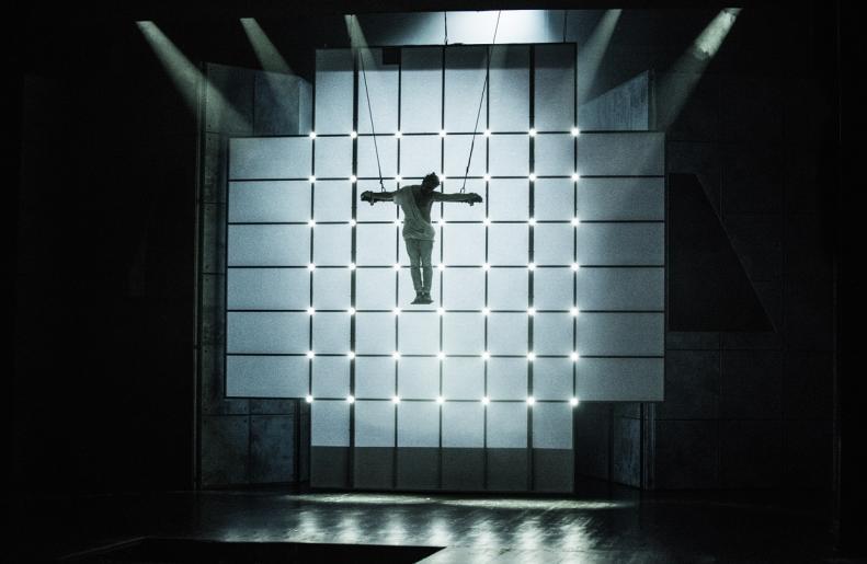 Fotografia przedstawia aktora odgrywającego rolę Jezusa, który został powieszony na tle podświetlonego krzyża.