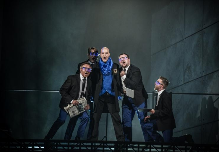 Na zdjęciu widzimy 5 mężczyzn w garniturach, charyzmatycznie śpiewających.