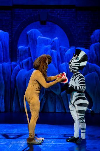 Fotografia przedstawia dwóch aktorów odgrywających rolę lwa i zebrę. Widzimy jak lew podaje zebrze steka.